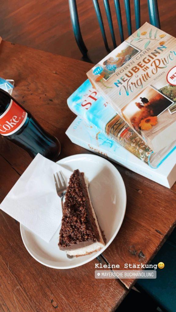 Buchhandlung mit Café, Kuchen, Cola und drei Bücher am Tisch