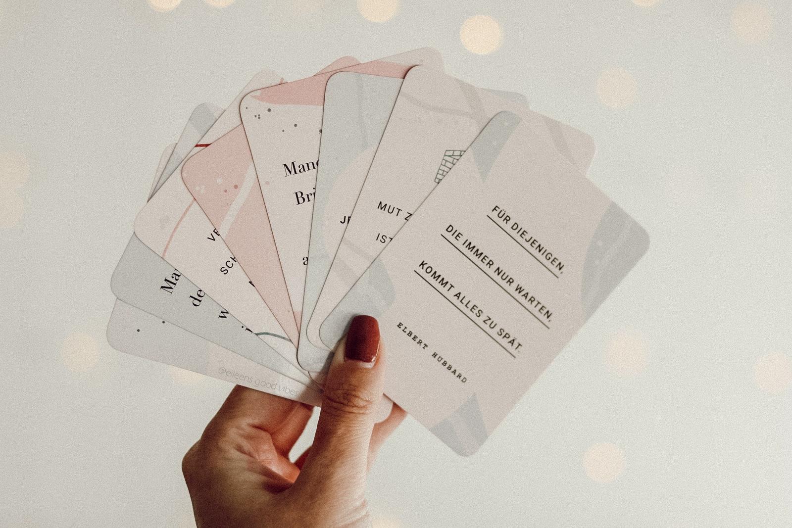 Kartenset Trau Dich Mut steht dir aufgefächert in der Hand vor einer Lichterkette